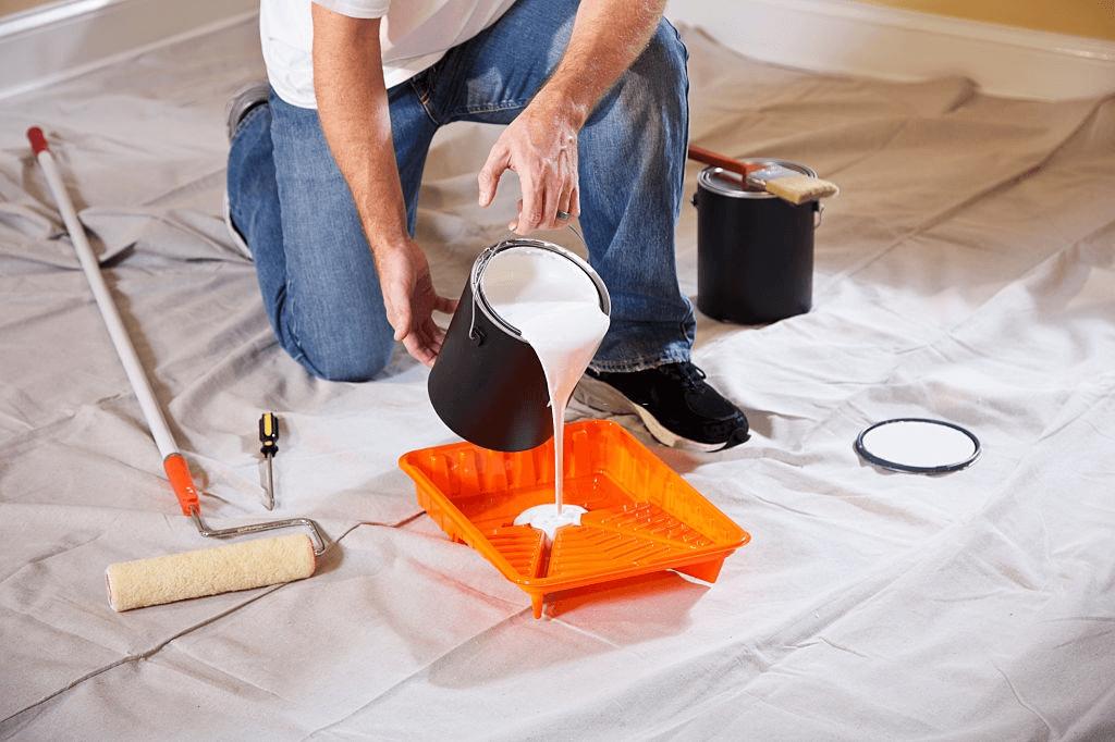 malarz nalewa farbę lateksową